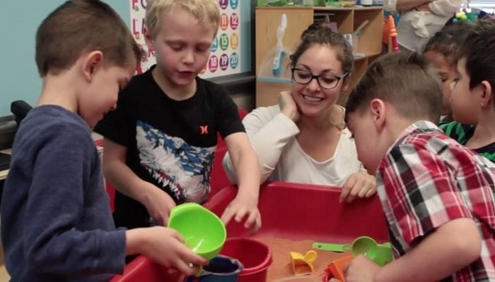 Female teacher with students learning math through play.