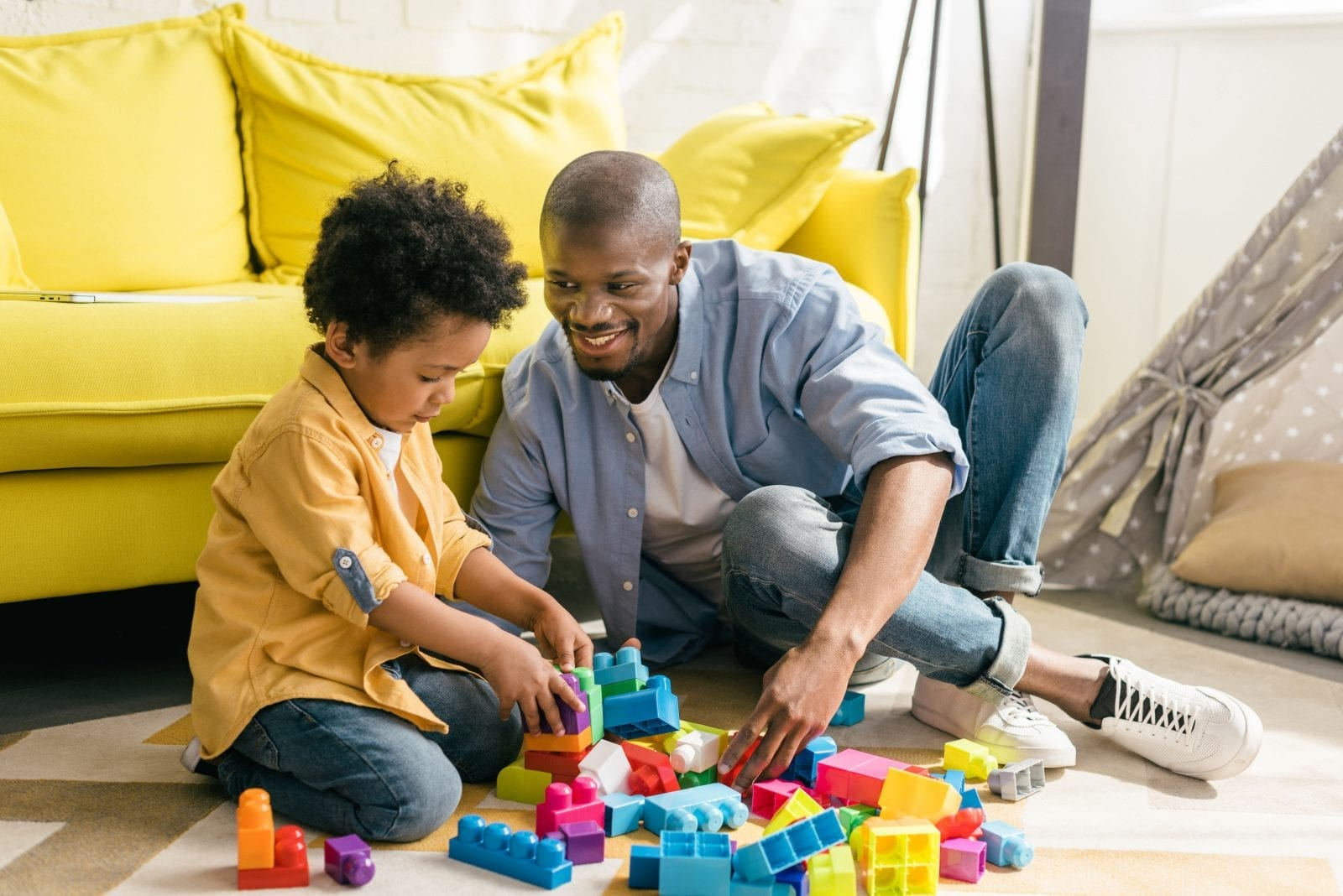 smiling african american father and little son playing with colorful blocks together at home